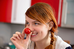 Young woman wearing clown nose, Munich, Bavaria, Germany