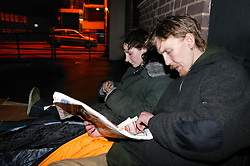 Homeless couple sleeping rough in the inner city streets; reading newspaper and settling down for the night,