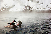A diver comes to the surface holding two King Crabs in his hands, at a lake in Jarfjord near Kirkeness, Finnmark region, northern Norway