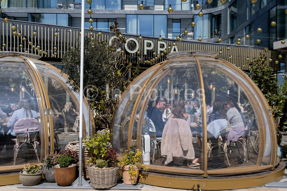 As Covid lockdown restrictions continue to ease and non-essential businsses re-open, customers enjoy al fresco dining at Coppa Club, a riverside restaurant located beneath luxury apartments near the Tower Of London, on 26th April 2021, in London, England. Coppa Club is part of the Strada-branded restaurant chain specialising in Italian cuisine.