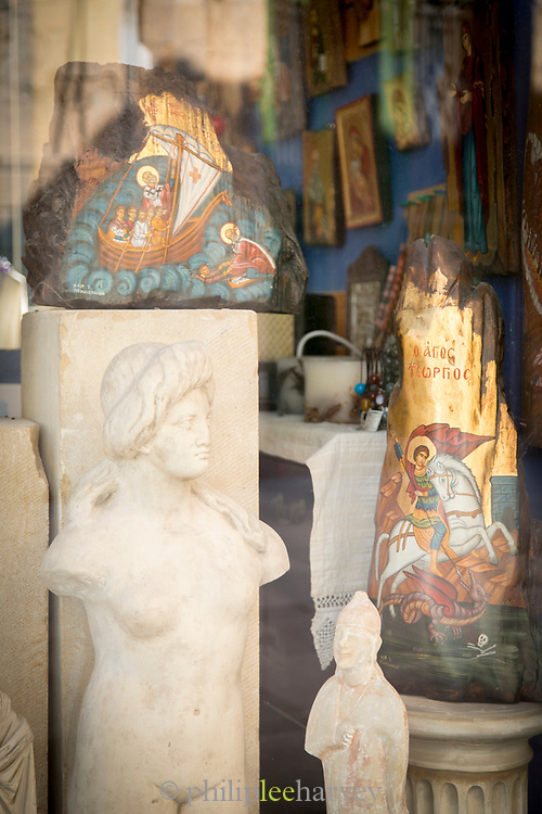 Shop window display including classical sculptures with religious art, Cyprus