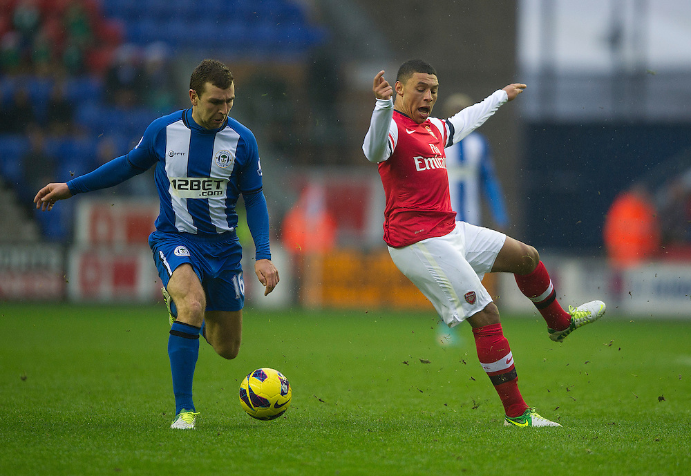Arsenal's Alex Oxlade-Chamberlain mis-cues his shot under pressure from Wigan Athletic's James McArthur ..Football - Barclays Premiership - Wigan Athletic v Arsenal - Saturday 22nd December 2012 - DW Stadium - Wigan..