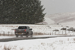 © Licensed to London News Pictures. 02/01/2021. Builth Wells, Powys, Wales, UK. Motorists drive along the Brecon road during a snowfall over the Mynydd epynt range near builth Wells in Powys, Wales, UK. UK. Photo credit: Graham M. Lawrence/LNP