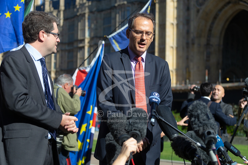Elliot Higgins, left, Founder of investigative website Bellingcat and investigator Christo Grozev, right are confronted by a protester, background, accusing them of working for NATO at a press conference on College Green opposite the Houses of Parliament. London, October 09 2018.