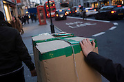 Two people push generic box sealed with green tape along London's Piccadily.