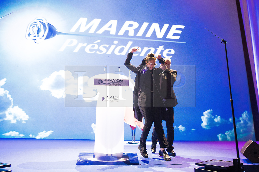 © Licensed to London News Pictures . 17/04/2017 . Paris , France . Despite heavy security a woman invades the stage and raises two middle fingers to the crowd from the podium before being pulled away from the stage and ejected from the auditorium . Marine le Pen's French far-right party , Front National , hold a meeting at the Zénith Paris arena , ahead of elections in France . Photo credit: Joel Goodman/LNP
