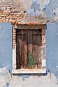 """Wood shutters on window in peeling blue wall. Burano, known for knitted lacework, fishing, and colorfully painted houses, is a small archipelago of four islands linked by bridges in the Venetian Lagoon, northern Italy, Europe. Burano's traditional house colors are strictly regulated by government. The Romans may have been first to settle Burano. Romantic Venice (Venezia), """"City of Canals,"""" stretches across 117 small islands in the marshy Venetian Lagoon along the Adriatic Sea in northeast Italy, between the mouths of the Po (south) and Piave (north) Rivers. Venice and the Venetian Lagoon are honored on UNESCO's World Heritage List."""