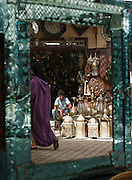 Reflections of daily life in a mirror for sale in the medina of Fes, Morocco