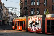 A modern De Lijn tram turns a corner on the tram network in central Ghent, Belgium.