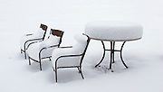 Table and chairs sit piled with snow.<br />