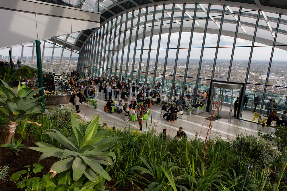 London skyline seen from the Sky Garden on the top of the Walkie Talkie building in the City of London. Visitors and plants are seen small with the expanse of wide architecture. 20 Fenchurch Street is a commercial skyscraper in London that takes its name from its address on Fenchurch Street, in the historic City of London financial district. It has been nicknamed The Walkie-Talkie because of its distinctive shape. Construction was completed in spring 2014, and the top-floor 'sky garden' was opened in January 2015. The 34-storey building is 160 m (525 ft) tall, making it the fifth-tallest building in the City of London. Designed by architect Rafael Viñoly and costing over £200 million.