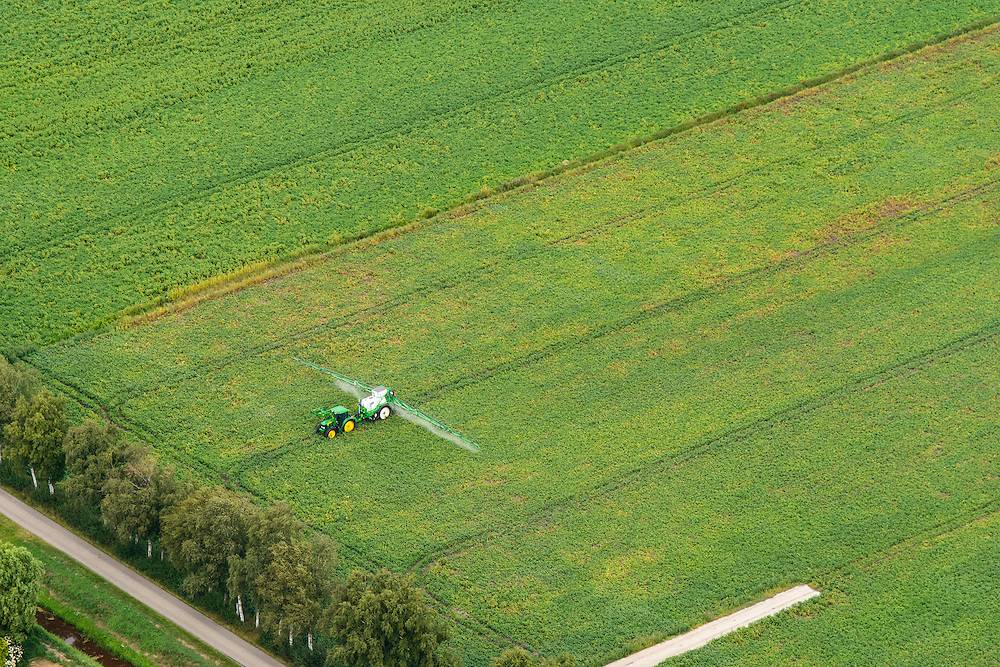 Nederland, Groningen, Stadskanaal, 27-08-2013;<br /> Landbouwer besproeit de aardappelplanten.<br /> Farmer sprays the potato plants.<br /> luchtfoto (toeslag op standaard tarieven);<br /> aerial photo (additional fee required);<br /> copyright foto/photo Siebe Swart.