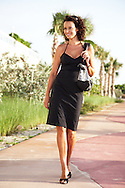 Lifestyle photo of a young woman enjoying a stroll on a palm lined street.