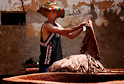 A man cleaning a load of leather that has been dyed at the famous tanneries of Fes, Morocco on Friday afternoon, June 08, 2007. The job of a tanner is quite prestigious and well respected; this man is wearing a traditional and colorful Berber hat. (PHOTO BY TIMOTHY D. BURDICK)