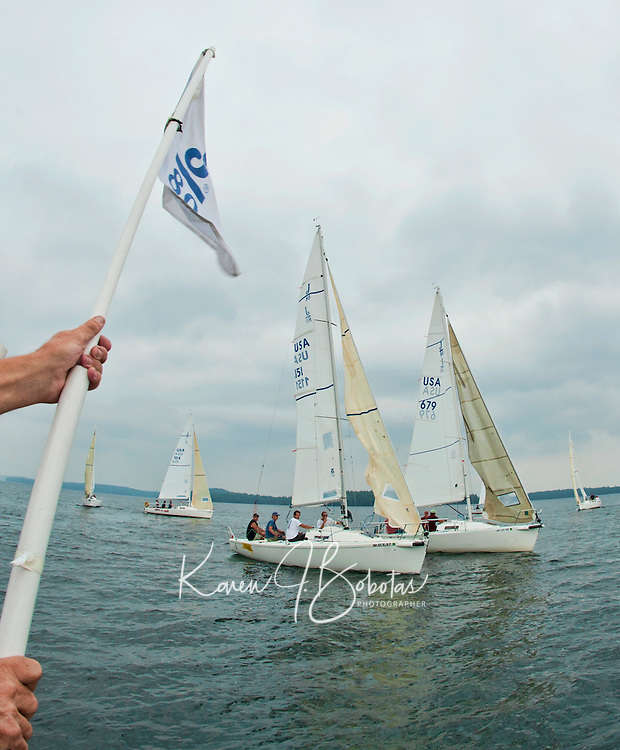 Adrian Curtis signals the beginning of the J80 sailboat race with flags for Winnipesaukee Yacht Club members Friday evening.  The group was able to get one race in before the storms came through the region.   (Karen Bobotas/for the Laconia Daily Sun)