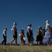 Locals pass by the Malaysia Airlines MH17 crash site in Grabovo, a small rural village in the province of Donetsk, eastern Ukraine. Malaysia Airlines flight MH17 was travelling from Amsterdam to Kuala Lumpur when it crashed killing all 298 on board including 80 children. The aircraft was allegedly shot down by a missile and investigations continue over the perpetrators of the attack.