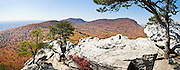 From atop Hanging Rock, you can view across a sea of autumn orange and red foliage to Moore's Wall, at Hanging Rock State Park in Stokes County, North Carolina, USA. (Panorama stitched from 3 images.) The eroded quartzite knob called Hanging Rock rises to 2150 feet elevation. The park is 30 miles (48 km) north of Winston-Salem, and approximately 2 miles (3.2 km) from Danbury. Hanging Rock State Park is located in the Sauratown Mountain Range, which is made up of monadnocks (or inselbergs, isolated hills) that are separated from the nearby Blue Ridge Mountains. Prominent peaks in the Sauratown range rise from 1,700 feet (520 m) to more than 2,500 feet (760 m) in elevation and stand in contrast to the surrounding countryside, which averages only 800 feet (240 m) in elevation. Named for the Saura Native Americans who were early inhabitants of the region, the Sauratown Mountains are the erosion-resistant quartzite remnants of mountains pushed up between 250 and 500 million years ago. Panorama stitched from 3 overlapping photos.