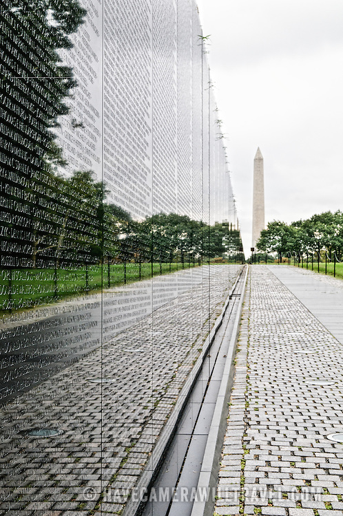 Names of those killed in action in Vietnam on the wall of the Vietnam Memorial in Washington DC with the Washington Monument in the background on an overcast day.