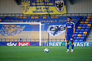 AFC Wimbledon defender Nesta Guinness-Walker (18) about to take a free kick in front of back to Plough Lane banner in stands during the EFL Sky Bet League 1 match between AFC Wimbledon and Hull City at Plough Lane, London, United Kingdom on 27 February 2021.