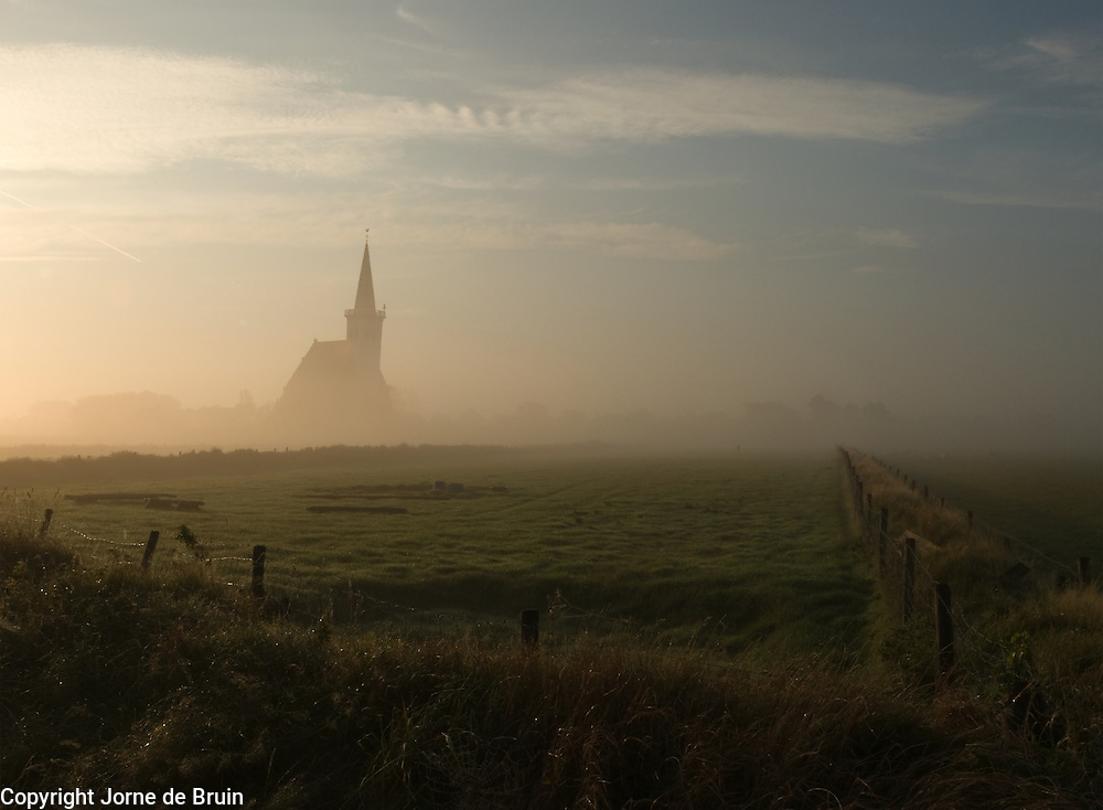 Early morning mist over field and church at Den Hoorn, Texel, the Netherlands