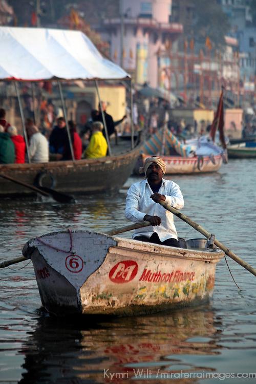 Asia, India, Varanasi. A man rows on the Ganges River in Varanasi.
