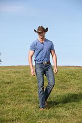cowboy walking on a grassy hill
