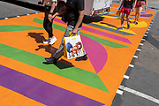 An anonymous male shopper carries a shopping bag for confectionary retailer M&Ms, over the multi-coloured markings of a crossing at Piccadilly Circus, on 16th July 2021, in London, England.