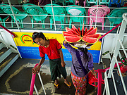20 NOVEMBER 2017 - YANGON, MYANMAR: A watermelon vendor on the Dala Ferry. There are vendors selling fruit, snacks, betel, toys, and phone SIM cards on the ferry. People getting off the Dala Ferry in Yangon leave the ferry terminal. Tens of thousands of commuters ride the ferry every day. It brings workers into Yangon from Dala, a working class community across the river from Yangon. A bridge is being built across the river, downstream from the ferry to make it easier for commuters to get into the city.     PHOTO BY JACK KURTZ
