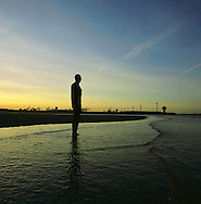 The sun rising behind one of the bronze statues of Antony Gormley's Another Place installation at Crosby, Merseyside at the mouth of the river Mersey. The Mersey is a river in north west England which stretches for 70 miles (112 km) from Stockport, Greater Manchester, ending at Liverpool Bay, Merseyside. For centuries, it formed part of the ancient county divide between Lancashire and Cheshire.