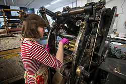 Lottie Small adds gold ink to the die stamping press at the workshop of Barnard and Westwood in London, who are printing the invitations for Prince Harry and Meghan Markle's wedding in May.