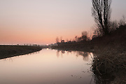 The River Parrett between Langport and Muchelney, as hte sun is setting, with mist starting to form in the distance.
