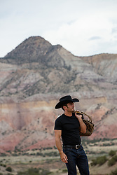rugged cowboy holding a duffle bag and lasso by a mountain range
