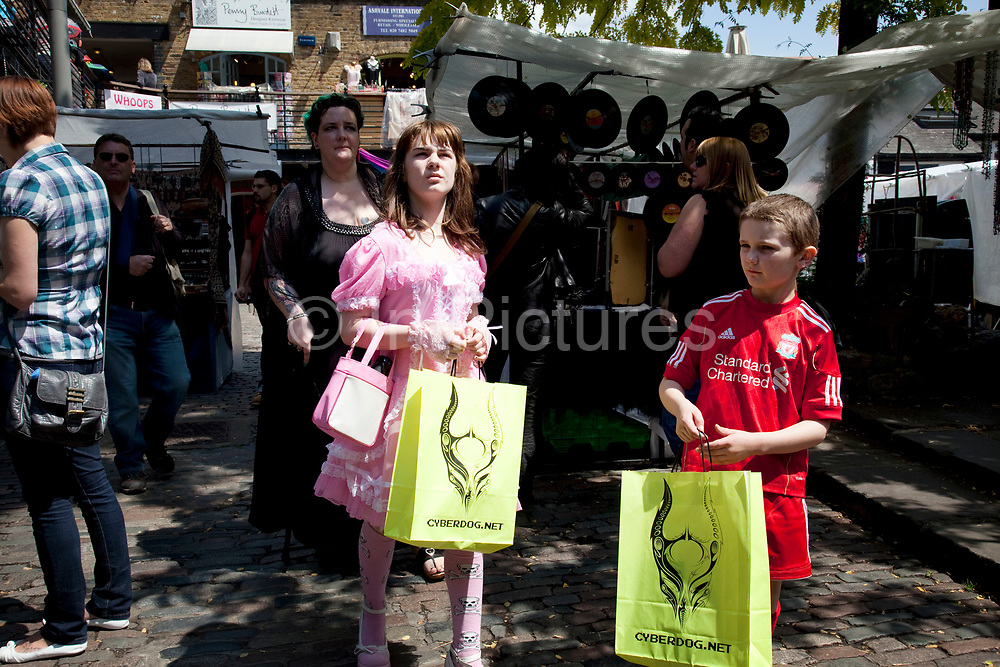 LONDON, ENGLAND, UK, JUNE 11TH 2011. Mother Louise Irwin-Ryan with her daughter Georgia (11, wearing a pink Lolita dress) and son Kiefer (8, wearing a red Liverpool Football Club kit) spending a day out together in Camden Town, North London. Having bought an inexpensive item each from their favourite shop 'Cyber Dog' the family walk back through the market to catch the bus home. Louise is on various benefits to help support her family income, and housing, although recent government changed to benefits may affect her family drastically, possibly meaning they may have to move out of London. Louise Ryan was born on the Wirral peninsula in 1970.  She moved to London with her family in 1980.  Having lived in both Manchester and Ireland, she now lives permanently in North London with her husband and two children. Through the years Louise has battled to recover from a serious motorcycle accident in 1992 and has recently been diagnosed with Bipolar Affective Disorder. (Photo by Mike Kemp/For The Washington Post)
