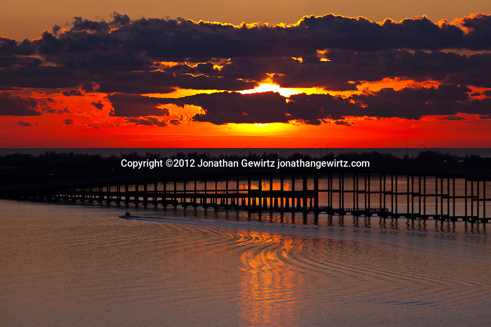The morning sun rises behind clouds over the Atlantic Ocean beyond Miami's Virginia Key, with the William Powell Bridge and Rickenbacker causeway across Biscayne Bay in the foreground. WATERMARKS WILL NOT APPEAR ON PRINTS OR LICENSED IMAGES.