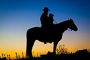 Silhouette of cowboy on horse, and his dog, at sunrise