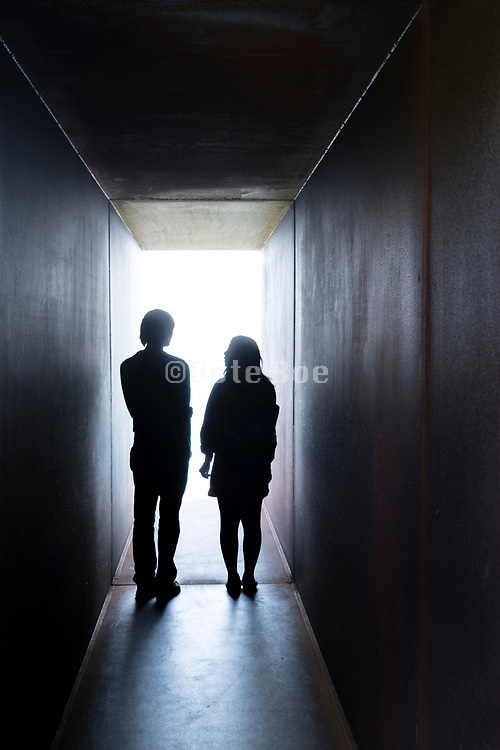 couple at the end of the strong light in a tunnel