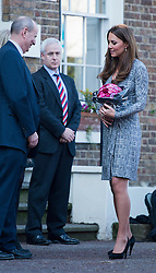 © London News Pictures. 19/02/2013. London, UK.  Catherine Duchess of Cambridge holding her stomach and carrying flowers as she leaves Hope House addiction centre for women in South London on February 19, 2013. The Duchess met clients and staff at Hope House, which is a 23-bed residential treatment centre for women with substance dependance. The Action Photo credit: Ben Cawthra/LNP