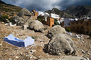 Graves lie in a cemetary besides the old town, or medina, of Chefchaouen, Morocco, with the Rif mountains visible in the background.
