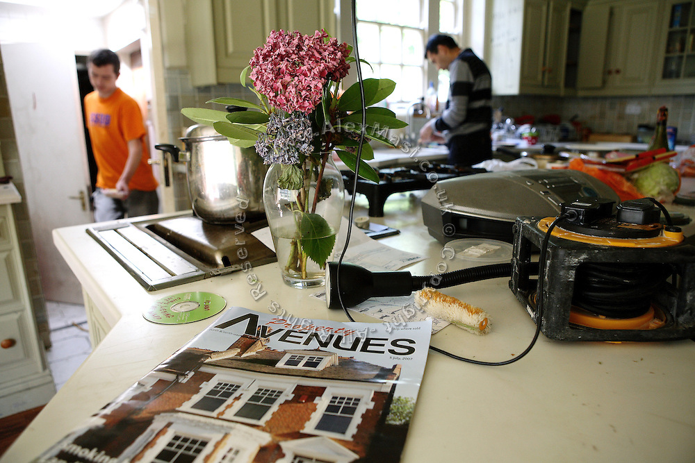 Lukatz, 23, from Poland, (left) is walking in the kitchen of the mansion on Ingram Avenue, while Kostica, 42, (right) from Romania, is washing dishes at the tap, on Friday, July 29, 2007, in Hampstead, London, England. Magazines with the latest property offers are still delivered regularly to the address. The 22-room mansion was last sold for UK£ 3.9M in 2002 and is now awaiting planning permissions to be demolished. Two new houses will soon be taking its place. Million Dollar Squatters is a documentary project in the lives of a peculiar group of squatters residing in three multi-million mansions in one of the classiest residential neighbourhoods of London, Hampstead Garden. The squatters' enthusiasm, their constant efforts to look after what has become their home, their ingenuity and adventurous spirit have all inspired me throughout the days and nights spent at their side. Between the fantasy world of exclusive Britain and the reality of squatting in London, I have been a witness to their unique story. While more than 100.000 properties in London still lay empty to this day, squatting provides a valid, and lawful alternative to paying Europe's most expensive rent prices, as well as offering the challenge of an adventurous lifestyle in the capital.
