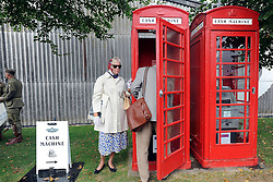 © Licensed to London News Pictures. 17/09/2011. GOODWOOD, UK. A couple use a cash machine installed in an old red telephone box. The Goodwood Revival at Goodwood in West Sussex today (17 September 2011). The revival is the world's largest historic motor race meeting, which relieves the 'glorious' days of the race circuit. Competitors and enthusiasts all dress in period fashion to enhance the experience. Photo credit : Stephen Simpson/LNP