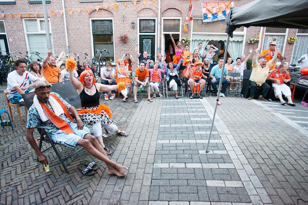 Bewoners van de Violenstraat in de Utrechtse volkswijk Ondiep, de wijk waar Wesley Sneijder vandaan komt, kijken op een scherm naar de WK finale van Nederland tegen Spanje.<br /> <br /> Supporters are watching the finals of the World Championship Soccer 2010 on the street in the Utrecht district Ondiep