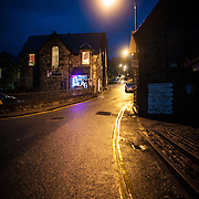 A night shot of a street after rain that run next to Harlech Castle in Harlech, Gwynedd, on the northwest coast of Wales next to the Irish Sea. The castle was built by Edward I in the closing decades of the 13th century as one of several castles designed to consolidate his conquest of Wales.
