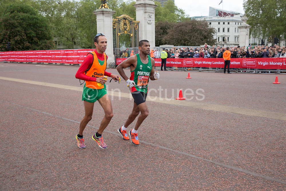 Portuguese para-athlete, Jorge Pina with his running guide, on The Mall during The Virgin London Marathon on 28th April 2019 in London in the United Kingdom. Now in it's 39th year, the London Marathon is a large sporting event with over 40,000 runners expected to take part.