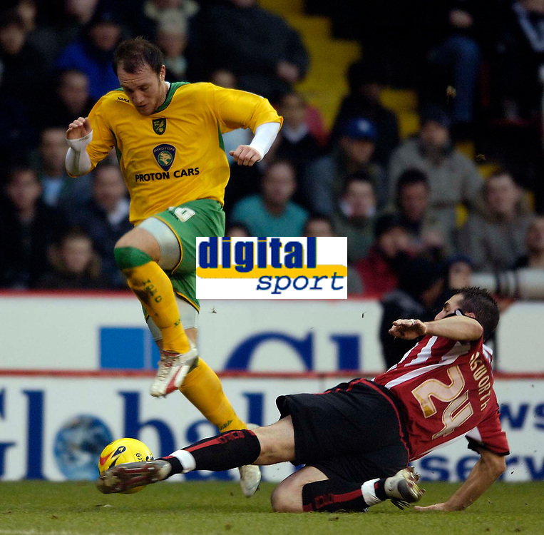 Photo: Jed Wee.<br />Sheffield United v Norwich City. Coca Cola Championship.<br />26/12/2005.<br />Norwich's Dean Ashton (L) is tackled by Sheffield United's David Unsworth.