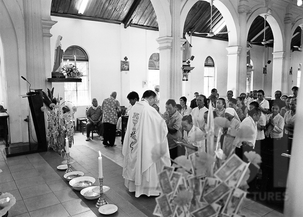 A priest gives wafers to worshipers during a mass in a church of Vientiane, Laos, Asia