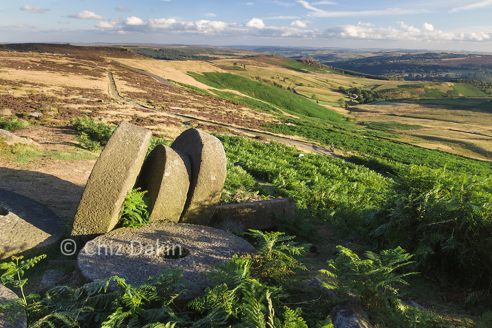Abandoned millstones and part-worked trough on Stanage Edge, with distant views of Millstone Edge and Over Owler Tor in the background (summer)