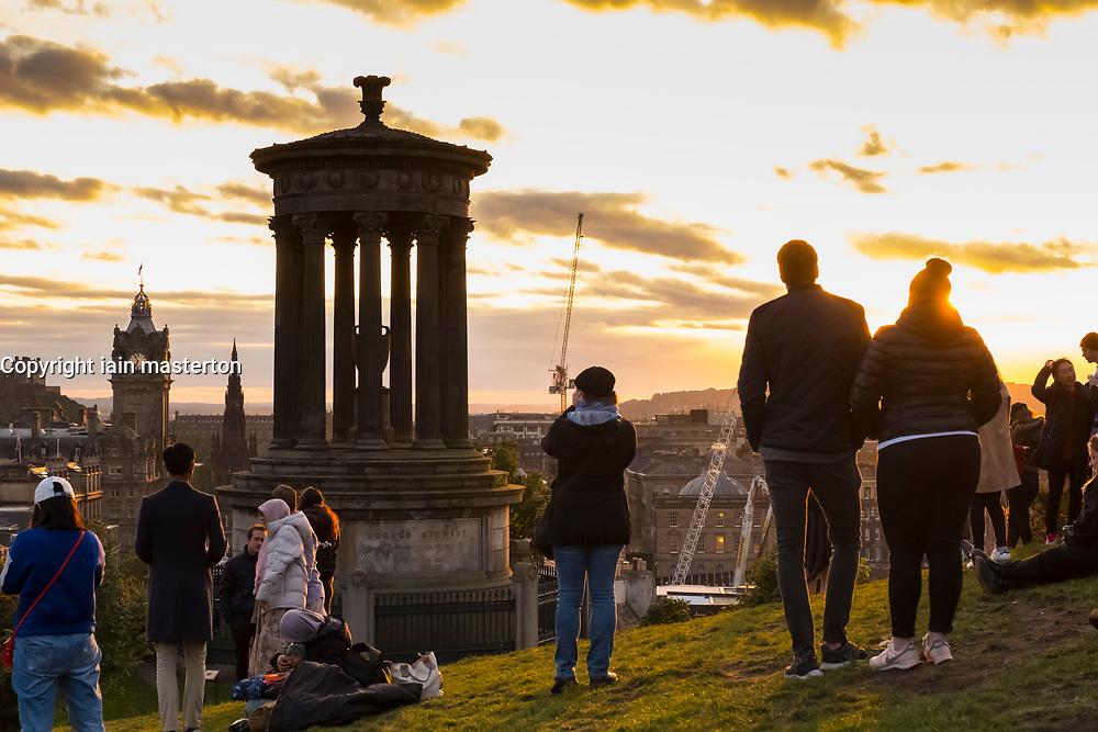 Tourists gather on Calton Hill to watch the sunset over Edinburgh, Scotland, United Kingdom.