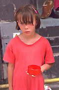 Girl age 10 looking depressed holding out dish for donations.  Torun Poland