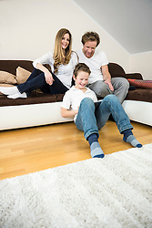Happy family in living room with digital tablet