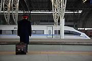 A high-speed train driver waits on the platform of  the rail station in Nanjing, China on 04 March, 2011.  In just a few years, China has built the world's longest high-speed rail network, named China Rail High-speed (CRH), and continues to expand despite accusations of technology pilfering and safety concerns. On July 23rd, 2011, two high-speed trains in eastern China collided due to supposed malfunctioning in the signaling system, killing 40 and injuring hundreds, meanwhile a slew of corruption scandals at China's rail ministry has surfaced recently.